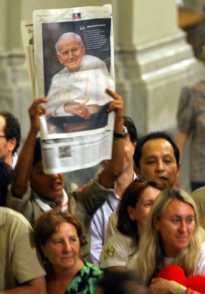 A person holds a photo of the late Pope John Paul II during a ceremony in the Basilica of St. John Lateran in Rome on Tuesday.  (Associated Press / The Spokesman-Review)