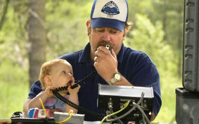Tom Rose of the Spokane County Amateur Radio Emergency Service holds his 9-month-old daughter, Shelby, as he tries to make contact with a radio operator in San Francisco, Saturday afternoon in Valleyford County Park.   (Dan Pelle / The Spokesman-Review)