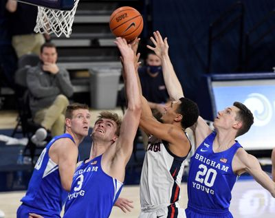 Gonzaga's Jalen Suggs takes on BYU defenders Mat Haarms (3) and Spencer Johnson (20) at the rim during Thursday's West Coast Conference win.  (By Colin Mulvany / The Spokesman-Review)