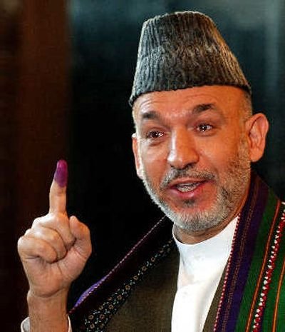 Afghan President Hamid Karzai shows his inked finger before voting in Kabul on Sunday.   (Associated Press / The Spokesman-Review)