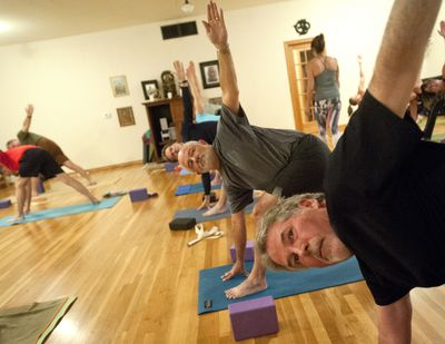 Pat Lacy, right, and Jim Millgard, center, practice yoga on Tuesday at Yoga Shala studio on the South Hill in Spokane. (Tyler Tjomsland)