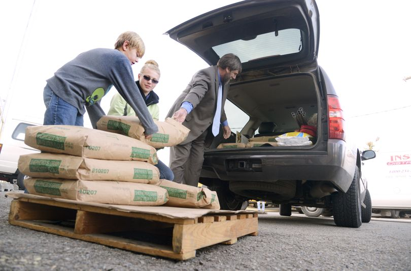 East Valley School District Superintendent John Glenewinkel, right, helps Summer Romney and Liam Nowles unload 400 pounds of flour at the district's warehouse on Tuesday. Wheat from the East Valley Community Garden was ground into flour for use in school lunches. (Colin Mulvany)