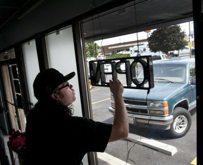 """FILE – Daniel Wendling, of Satori, hangs the """"open"""" sign in the store's window moments before opening their door for the first time on Friday, Aug. 8, 2014, in Spokane. Washinton Marijuana businesses will have to abide by a new set of rules after a bill was signed Tuesday, May 16, 2017 by Gov. Jay Inslee. (Dan Pelle / The Spokesman-Review)"""