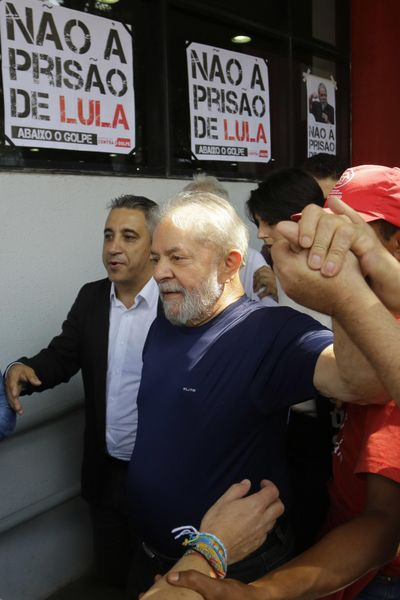 Brazil's former President Luiz Inacio Lula da Silva greets supporters as he walks in front of the metal workers union headquarters in Sao Bernardo do Campo, Brazil, Saturday, April 7, 2018. The once wildly popular leader, who rose from poverty to lead Latin America's largest nation, had until 5 p.m. local time Friday, to present himself to police in the city of Curitiba to begin serving a sentence of 12 years and one month for a corruption conviction. (Nelson Antoine / Associated Press)