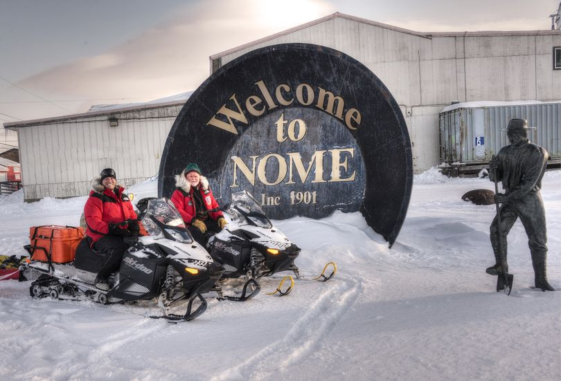 Josh Rindal of Spokane and Bob Jones pose with their snowmobiles  at the world's biggest gold pan in Nome. Rindal and Bob Jones of Kettle Falls were snowmobiling 1,400-miles along the route of Alaska's famous Iditarod Sled Dog Race in March 2014. (Robert Jones)