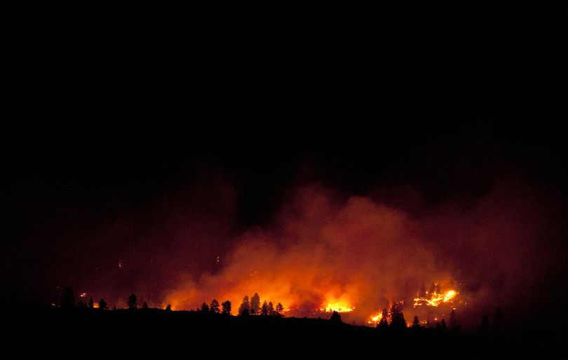 A fire rages in the hills outside Carlton, Washington, on Sunday morning. The Carlton Complex fire has burned more than 240,000 acres. (Tyler Tjomsland)