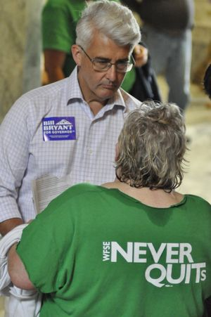 OLYMPIA -- GOP gubernatorial candidate Bill Bryant talks with state employee during a rally for higher wages and better benefits in the Capitol Rotunda.  (Jim Camden/The Spokesman-Review)
