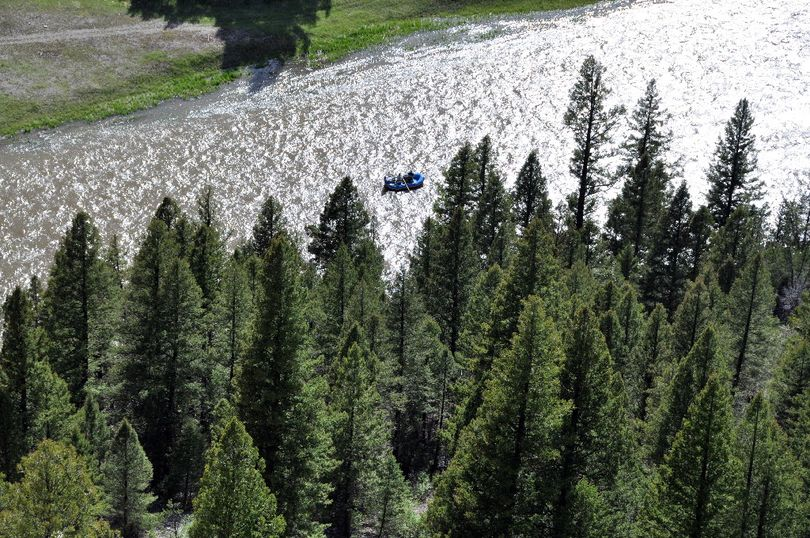 A raft carring anglers is put in perspective in this shot from high above on top of a rock cliff overlooking the Smith River. (Rich Landers)