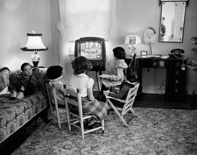 In this Jan. 6, 1953,  photo, four schoolchildren watch a teacher give them a lesson via television at home in Baltimore, Md. TV was key to the world baby boomers were born into: a  modernized world whose  problems all  seemed to have  available solutions. (Anonymous / Associated Press)