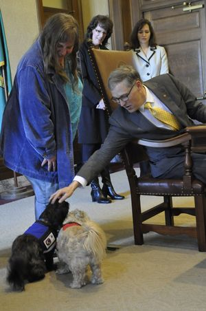"""OLYMPIA -- Gov. Jay Inslee stops to pet Huckleberry, left, and Huey, a pair of service dogs who attended a bill signing Wednesday in the Capitol. The two service dogs were there with Darly Abbott of Olympia for  a bill making it a felony for employers to coerce workers into """"involuntary servitude"""" by threatening to destroy their work documents or report them to authorities. (Jim Camden)"""