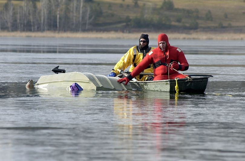 Rescuers retrieve an overturned boat on Hauser Lake in 2004 after two hunters capsized while shooting at ducks. The men survived. Victims of other winter boating mishaps haven't been so lucky. (File)