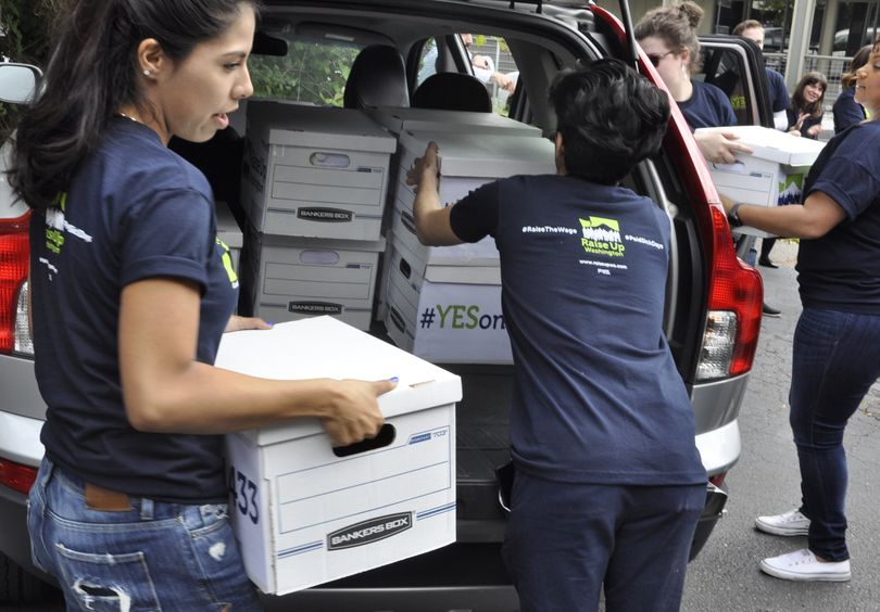OLYMPIA -- Volunteers for Initiative 1433, which would raise the state minimum wage and guarantee paid sick leave for many workers in Washington, deliver boxes of signed petitions to the state Elections Office Wednesday morning. (Jim Camden/The Spokesman-Review)