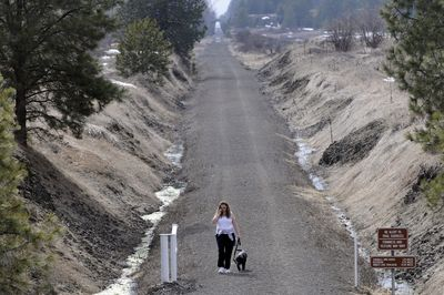 Michele Deyette and her dog Atticus  stroll  along the Columbia Plateau Trail  in Cheney on Thursday. This summer, federal stimulus funds will begin paving the Fish Lake Trail, which will connect Spokane and nearby Fish Lake.  The Fish Lake Trail is managed by the cities of Spokane and Cheney.  (Jesse Tinsley / The Spokesman-Review)