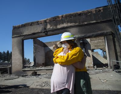 Washington Commissioner of Public Lands Hilary Franz, right, embraces Malden Mayor Chris Ferrell on Sept. 9 in front of a burned-out building in Malden, Washington. Franz toured the town and made the case for more funding for firefighting resources. Most of the buildings in Malden were destroyed by wind-driven wildfire Sept. 7.  (Jesse Tinsley/The Spokesman-Review)