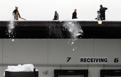 Victoria Hanko, Nick DiBartolo, Jason Clark, Rod Wieber and Rick Gallinger shovel off the roof of the Second Harvest Inland Northwest warehouse  on Monday.  (Jesse Tinsley / The Spokesman-Review)
