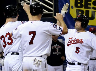 Twins Justin Morneau, left, and Joe Mauer, center, greet Michael Cuddyer, right, after his homer. All three went long Saturday.  (Associated Press / The Spokesman-Review)