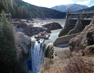 An excavator chips away at the Glines Canyon Dam, 13 miles upriver from the mouth of the Elwha River, near Port Angeles, Wash., in March. (Associated Press)