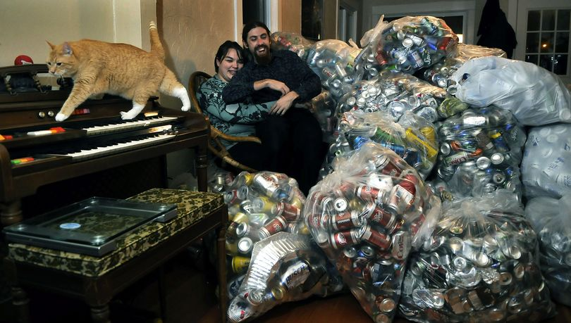 Andrea Parrish and Peter Geyer have collected about 4 percent of their 400,000-can goal. They plan to use recycling proceeds to fund their wedding. They have about 120 pounds of cans in the living room of their Spokane home, which they share with their cat, Smudgie. (Dan Pelle)
