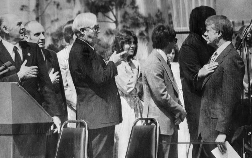 President Jimmy Carter momentarily looks the wrong way as the flag is raised during his  May 1978 visit to Spokane's Riverfront Park.  King Cole, a major influece in bringing Expo '74 to Spokane, points the direction to president should be facing. Interior Secretary Cecil Andrus (left) and former Spokane Mayor David Rodgers (second from left) watch the ceremony.  (Photo Archive / Spokesman-Review Archives)