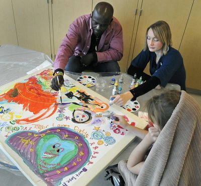 Nicholas Sironka, visiting artist (left) and Ann Walker, Arts in Healing coordinator at Providence Sacred Heart Medical Center, work on piece with a patient in the Children's Hospital, October 27, 2010 in Spokane, Wash. (Dan Pelle / The Spokesman-Review)
