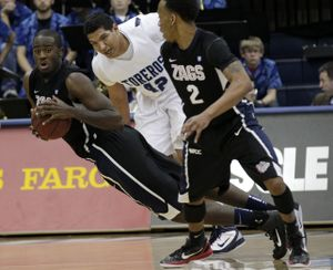 Gonzaga's Sam Dower, left, picks up a loose ball as San Diego's Chris Gabriel, center, and Gonzaga's Marquise Carter, right, look on in the first half of their NCAA college basketball game on Saturday, Feb. 26, 2011, in San Diego. (Gregory Bull / Associated Press)