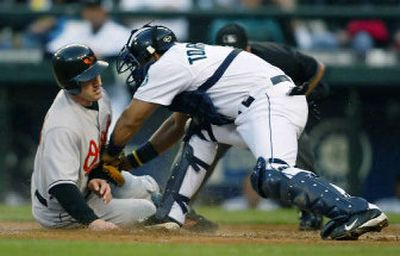 Mariners catcher Yorvit Torrealba tags out the Orioles' Jay Gibbons at the plate to end the top of the third inning.   (Associated Press / The Spokesman-Review)