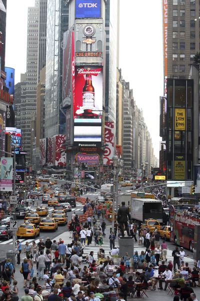 """Pedestrians and traffic make their way through New York's Times Square on Friday. The collision of avenues helped name this place the """"Crossroads of the World.""""  (Associated Press / The Spokesman-Review)"""