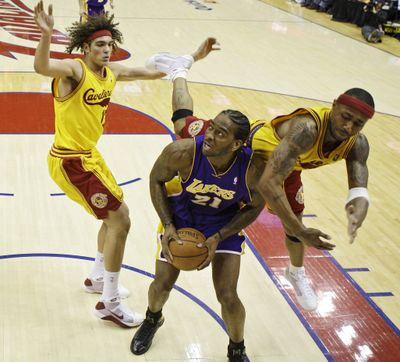 The Lakers' Josh Powell is fouled by Cleveland's Mo Williams, right.  (Associated Press / The Spokesman-Review)