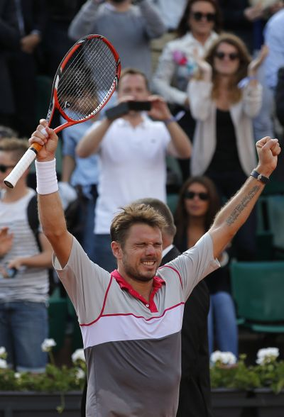 Stan Wawrinka raises arms in triumph at French Open on Tuesday. (Associated Press)