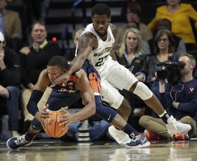 Wake Forest's Chaundee Brown, right, battles Virginia's Devon Hall for a loose ball in a January 2018 game. (AP)