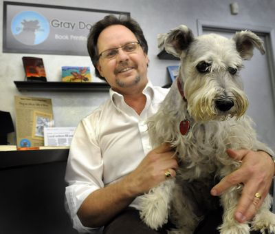 Russ Davis holds his gray dog, Zak, at his printing business, Gray Dog Press, a new publishing house in Spokane. (CHRISTOPHER ANDERSON / The Spokesman-Review)