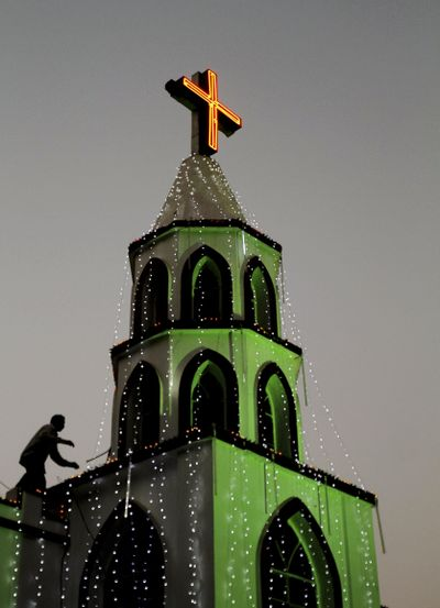 An Indian man decorates a church with lights ahead of Christmas in the eastern Indian city of Bhubaneswar, India, Monday, Dec. 23, 2013. (Biswaranjan Rout / AP)