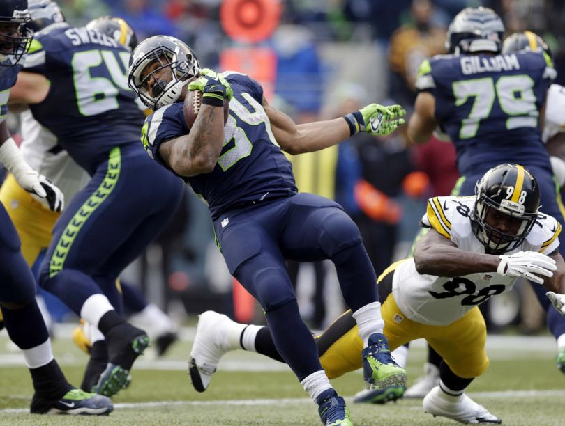 Seahawks' Thomas Rawls, left, rushes past Pittsburgh Steelers' Vince Williams in the first half of Sunday's game.