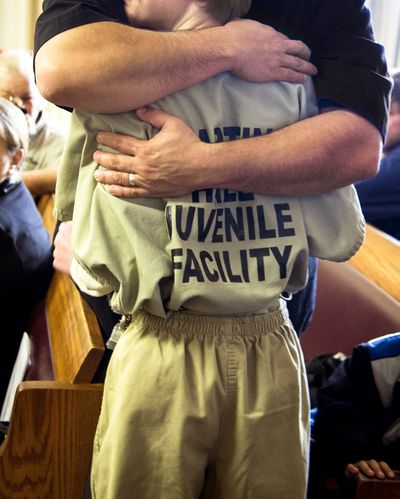 Kimo Morrison embraces the 11-year-old boy sentenced to four years in juvenile detention at the Stevens County Courthouse on Wednesday. The boy was convicted of plotting to kill a female classmate at Fort Colville Elementary in February. (Colin Mulvany / The Spokesman-Review)