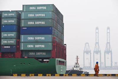 A worker walks past a cargo ship loaded with containers at the port in Tianjin, China, in March.  (Associated Press / The Spokesman-Review)