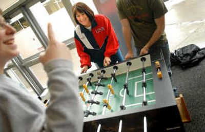 Kathy Brainard, center, plays foosball with students at Cheney High School last week. Brainard recently won third place in the world championships of foosball in Italy.   (Brian Plonka / The Spokesman-Review)