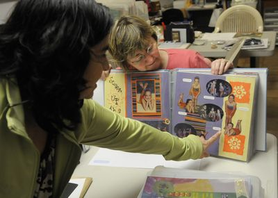Crystal Ray, right, shows off one of her scrapbooks to Adrianna Gmeiner during a  session at Ray's home on April 24 in south Spokane. (Dan Pelle / The Spokesman-Review)