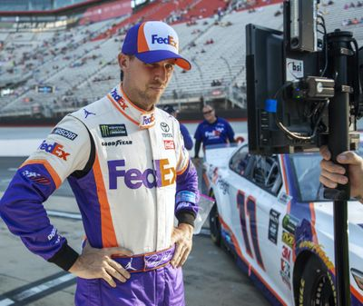 Denny Hamlin watches a television monitor as the last car qualifies for the NASCAR Cup Series auto race, Friday, Aug. 16, 2019, at Bristol Motor Speedway in Bristol, Tenn. Hamlin won the pole for Saturday night's race. (David Crigger / Bristol Herald Courier via AP)