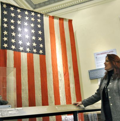 """Secretary of State Kim Wyman in front of a rare 42-star flag, which would have been used from November 1889 to July 1890, when Idaho became a state. The flag is part of the """"Blazes, Rails and the Year of Statehood"""" exhibit. (Jim Camden)"""