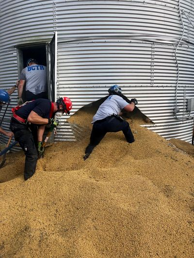 In this May 30 photo provided by the Ross Township Fire Department, rescue personnel shovel soybeans out of the bottom of a bin during an effort to rescue farmer Jay Butterfield, who was buried up to his neck inside. (Associated Press)