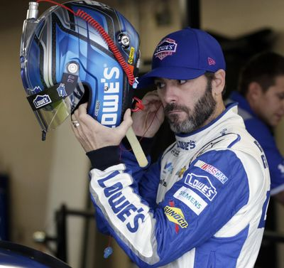 NASCAR Sprint Cup Series auto racing driver Jimmie Johnson prepares to don his helmet for a practice session at Kansas Speedway in Kansas City, Kan., Friday. (Colin E. Braley / Associated Press)