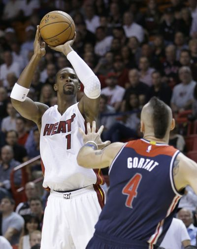 Chris Bosh, left, scored 26 points and grabbed 15 rebounds in Miami's win. (Associated Press)