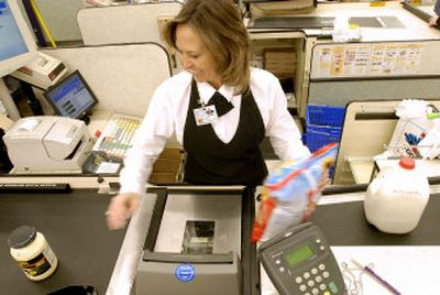 Kelli Ormesher scans grocery items at Super 1 Foods in Coeur d'Alene in January. Gov. Butch Otter proposed a targeted grocery tax credit to give a big credit to low-income Idahoans, but lawmakers on the House tax committee rejected it in favor of a pricier proposal from Rep. Cliff Bayer, R-Boise, to raise the credit for everyone.    (Jesse Tinsley / The Spokesman-Review)