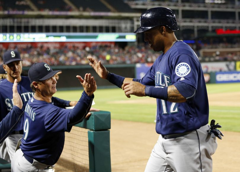 Seattle Mariners' Leonys Martin is congratulated by manager Scott Servais (9) after Martin scored on a Nori Aoki single in the seventh inning of a baseball game against the Texas Rangers on Tuesday, April 5, 2016, in Arlington, Texas. (Jim Cowsert / Associated Press)