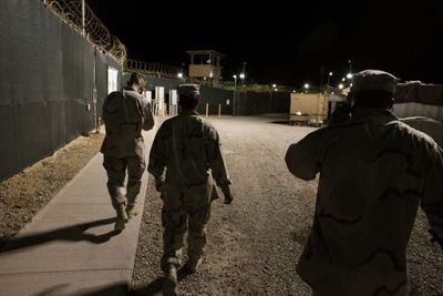 In this photo reviewed by the U.S. military, military personnel walk along the internal perimeter fences at  the Camp 4 detention facility  at Guantanamo Bay U.S. Naval Base.  (Associated Press / The Spokesman-Review)
