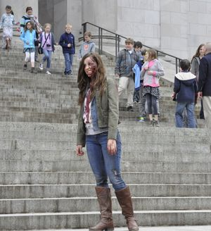 OLYMPIA -- Heather Hatton, an actress in a commercial supporting the state's tax incentive for films shot in Washington, prepares for a take on the Capitol steps as students on a tour stream past. (Jim Camden)