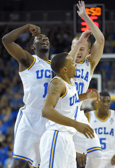 UCLA's Isaac Hamilton, left, Bryce Alford, upper right, and Norman Powell celebrate a victory. (Associated Press)