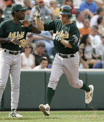 Oakland's Mark Ellis, right, is congratulated by third base coach Ron Washington after hitting a home run.    (Associated Press / The Spokesman-Review)