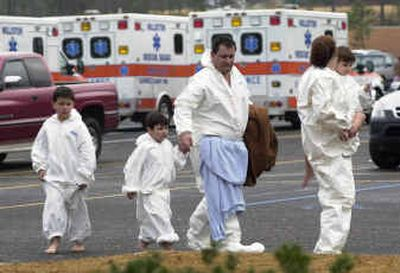 The Stiefel family, from left,  Alex, Christopher, Karl, Lisa and Karlee, walk away after going through the decontamination process at University of South Carolina-Aiken on Thursday in Aiken, S.C. The Stiefel family was evacuated from Graniteville, S.C., after being exposed to chlorine gas from a train derailment.    (Associated Press / The Spokesman-Review)