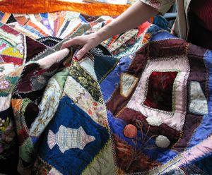 An appraiser examines a vintage quilt at the MAC Appraisal Days event in Spokane. (Cheryl-Anne Millsap / Photo by Cheryl-Anne Millsap)